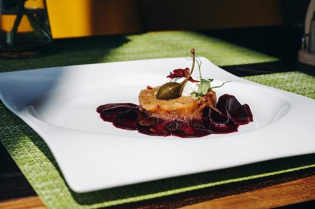 하얀 접시에 사탕무를 곁들인 파이크 타르타르