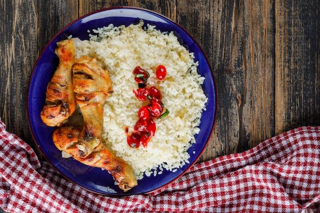 Pilaf in un piatto con carne di pollo, mirtilli rossi sul telo in legno e cucina