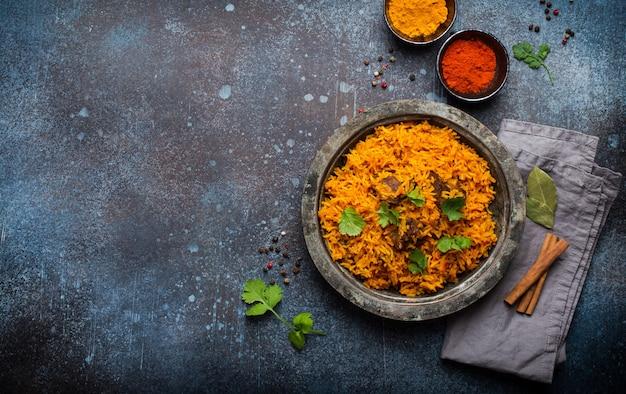 필라프 - 소박한 배경에 신선한 실란트로, 소스, 향신료를 곁들인 빈티지 접시에 쌀, 야채, 고기로 만든 전통 동양 요리, 위쪽 전망, 텍스트 공간