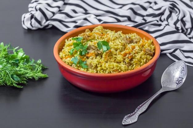 Плов с говядиной, морковью, луком, чесноком, перцем и тмином. традиционное блюдо азиатской кухни. выборочный фокус