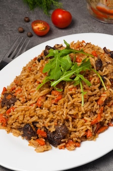 Pilaf with beef on a white plate in a restaurant