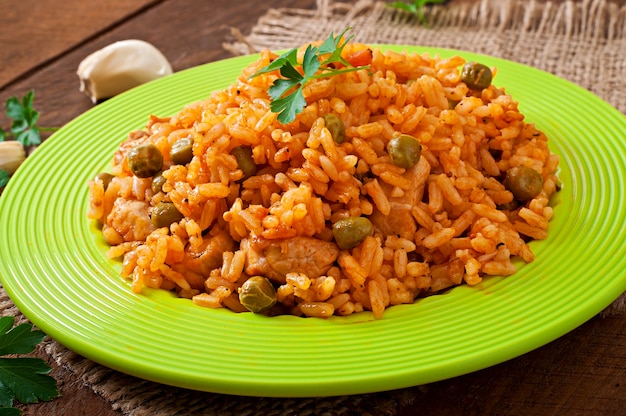 Pilaf with chicken, carrot and green peas on white plate