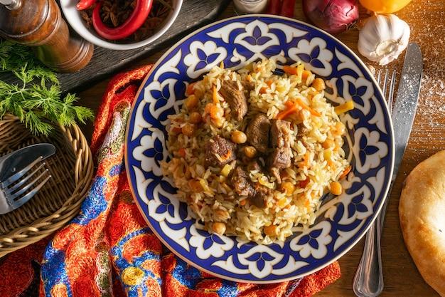 양고기와 필라프. 쌀, 양고기, 노란색 당근, 마늘, 건포도, 병아리 콩, 심황을 전통 동 양식 뜨거운 요리로 접시에 담아 우즈베키스탄 전통 장식으로 장식했습니다.