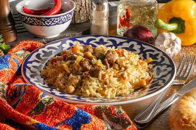 Плов с бараниной. традиционное восточное горячее блюдо из риса, баранины и желтой моркови с чесноком, изюмом, нутом и куркумой в тарелке с национальным узбекским орнаментом.