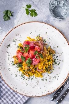 고기, 토마토, 양파를 곁들인 필라프. 접시에 우즈베키스탄 음식. 평면도