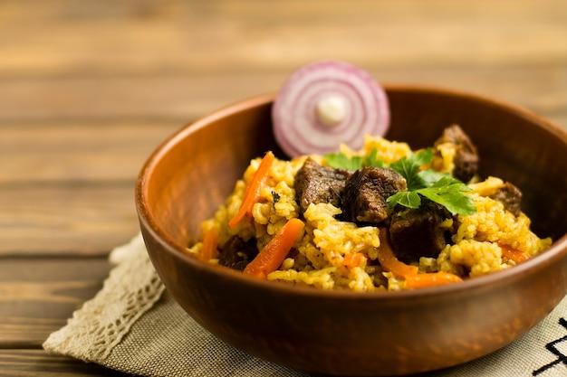 나무 테이블에 접시에 고기, 야채, 양파, 향신료와 필라프.