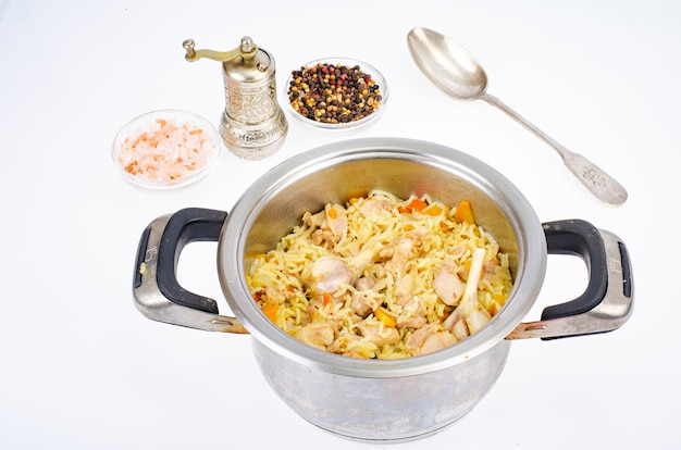 Pilaf with rice and meat in saucepan.