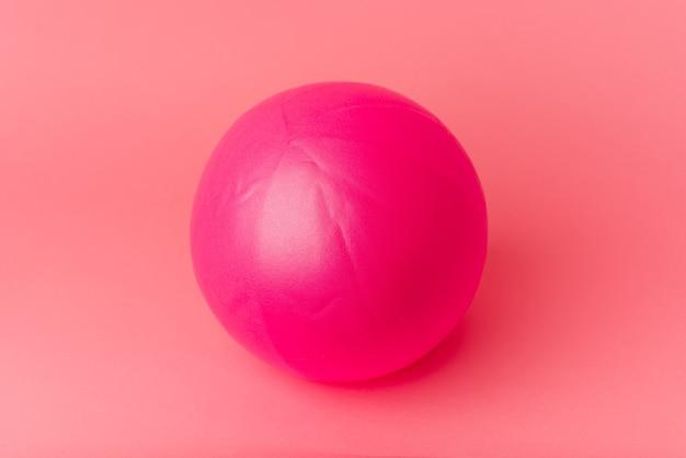 ピンクの背景に分離されたピラティスボール
