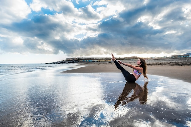 Pilates fitness have care of body rest and stay position for young caucasian woman on the shore at the beach scenic image for body health concept yoga balanced in contact and feeling with the nature