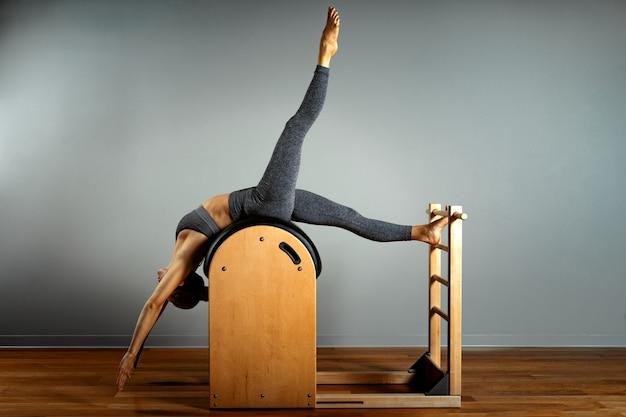 필 라 테 스, 피트 니스, 스포츠, 교육 및 사람들 개념-작은 배럴에서 운동을하는 여자. 임 펠트 장치의 수정, 올바른 자세.