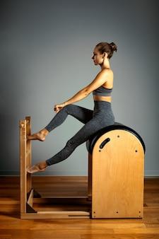 ピラティス、フィットネス、スポーツ、トレーニング、そして人々のコンセプト-小さな樽でエクササイズをしている女性。推進装置の修正、正しい姿勢。