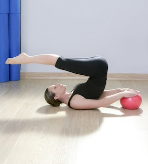 Pilates instructor woman with stability ball doing gym fitness yoga exercises