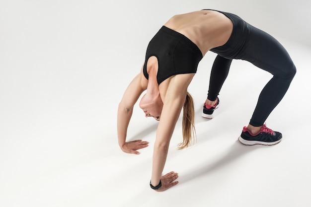 Pilates pose. athletic woman doing hard exercising. indoor shot, gray background