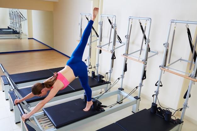 Pilates reformer woman arabesque exercise