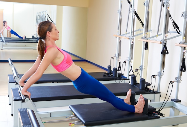 Pilates reformer woman long back stretch exercise