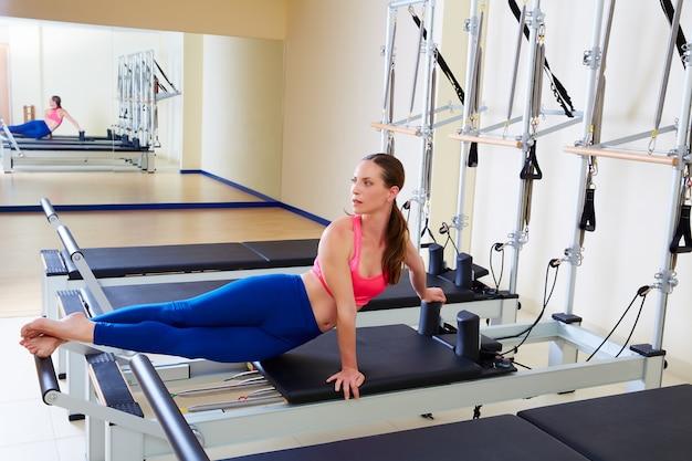 Pilates reformer woman snake twist exercise