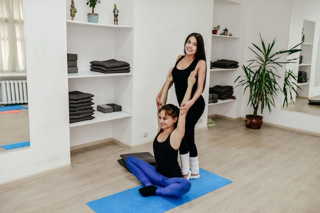 Учитель пилатеса помогает молодой женщине делать упражнения на растяжку
