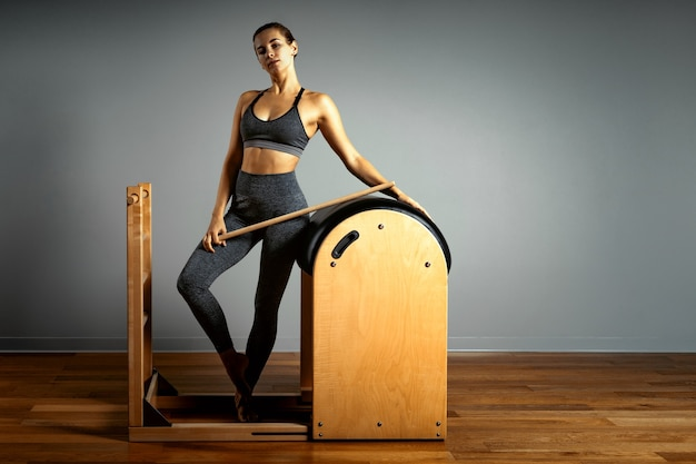 Pilates trainer exercises on a pilates barrel. body training, perfect body shape and posture correction opporno motor apparatus. copy space. woman doing exercises on ladder barrel.