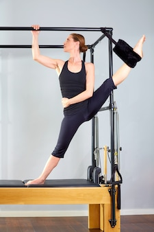 Pilates woman in cadillac split legs stretch exercise