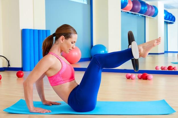 Pilates woman hip twist magic ring exercise