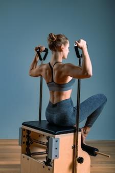 ジムでストレッチ体操を行うキャデラックリフォーマーのピラティス女性。フィットネスの概念、特別なフィットネス機器、健康的なライフスタイル、プラスチック。コピースペース、広告用スポーツバナー