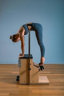 ジムでストレッチ体操を行う改革者のピラティス女性。フィットネスの概念、特別なフィットネス機器、健康的なライフスタイル、プラスチック。コピースペース、広告のスポーツバナー