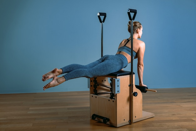Pilates woman in a reformer doing stretching exercises in the gym. fitness concept, special fitness equipment, healthy lifestyle, plastic. copy space, sport banner for advertising