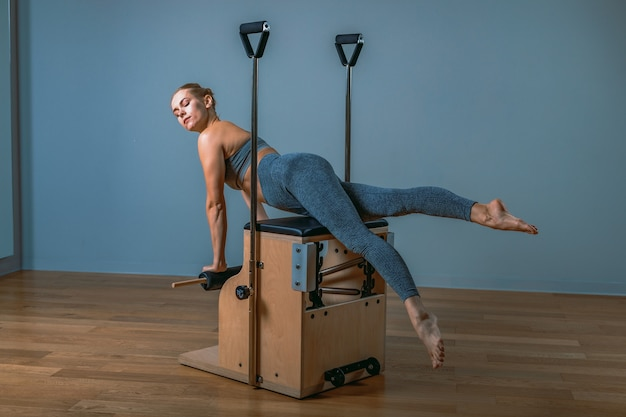Pilates woman in a reformer doing stretching exercises in the gym. fitness concept, special fitness equipment, healthy lifestyle, plastic. copy space, sport banner for advertising.