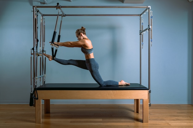 Pilates woman in reformer teaser exercise in gym indoors
