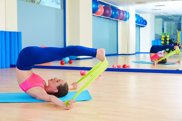 Pilates woman roll over rubber band exercise