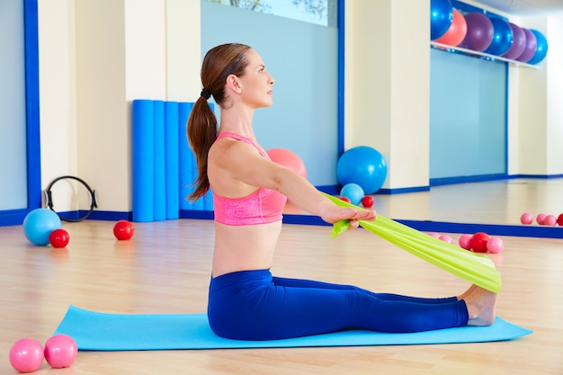 Pilates woman rowing rubber band exercise