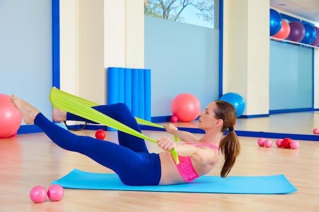 Pilates woman single leg stretch rubber band