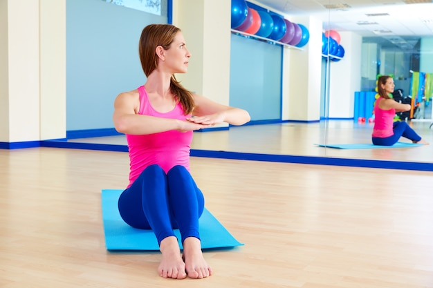 Pilates woman spine twist exercise workout at gym