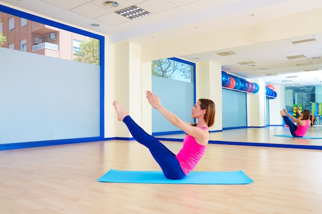 Pilates woman teaser exercise workout at gym