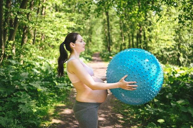 Красивая молодая беременная женщина делая работать с шариком pilates фитнеса голубым в парке напольном