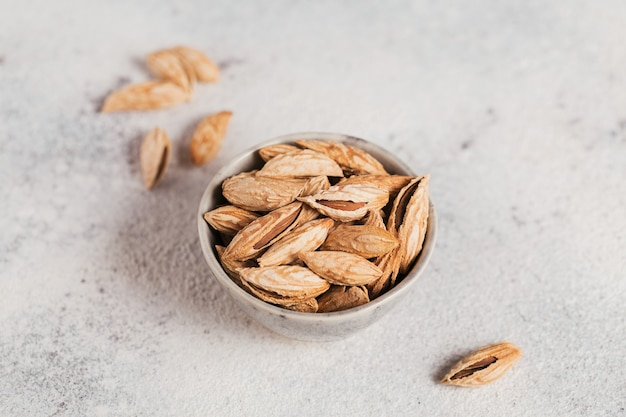 Pile of almond nuts in a bowl on a white background. fresh nuts in their shells.