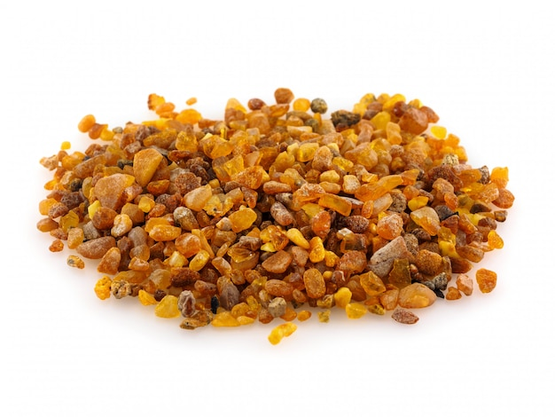 A pile of amber stones on a white background. a handful of yellow amber.