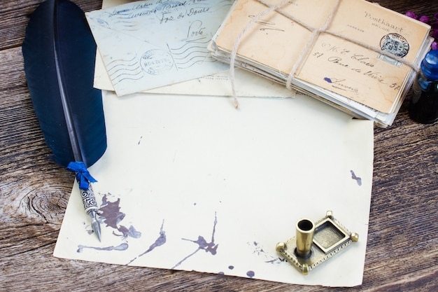 Pile of antique letters with ink stains and blue feather pen