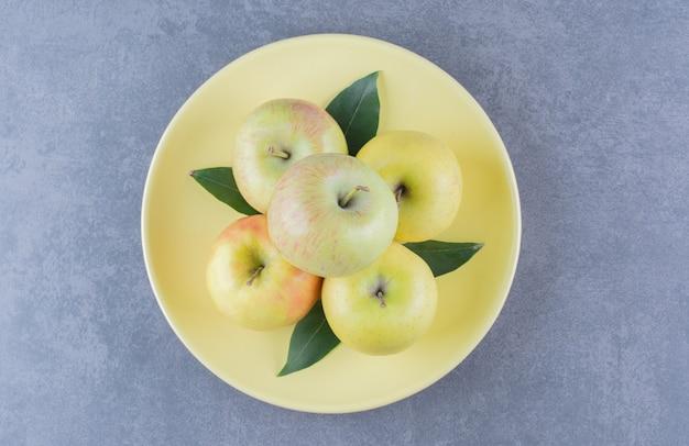 Un mucchio di mele su un piatto sul tavolo di marmo.