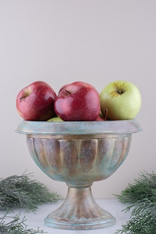 Pile of apples in a metal vase on white surface