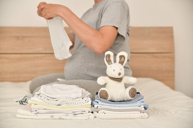 Pile of baby clothes with a rabbit and pregnant woman