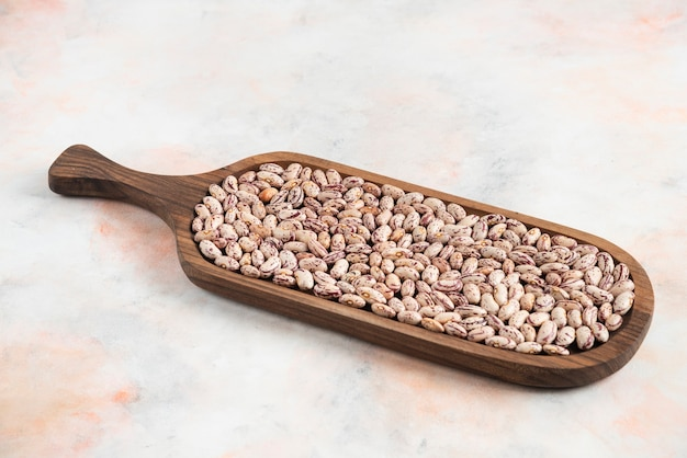 Pile of beans in wooden tray over white surface.
