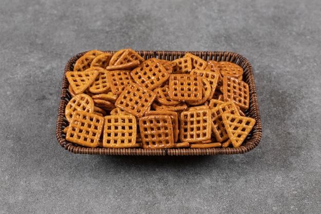 Pila di biscotti nel cestello su superficie grigia.