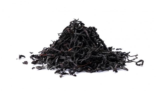 Pile of black tea leaves scattered on white table