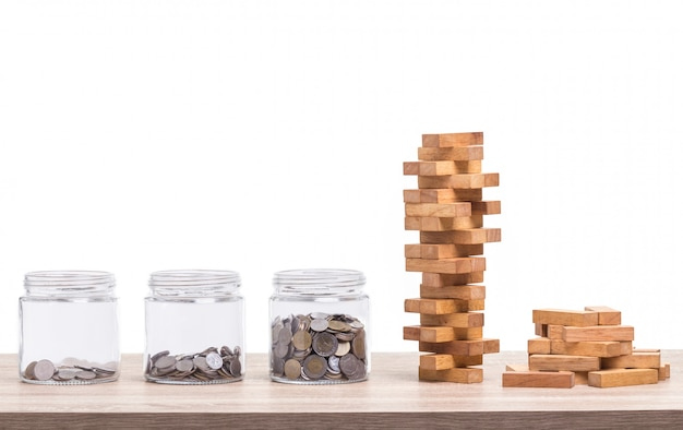 Pile of blocks wood game and jar of coin piggy bank on wooden table.