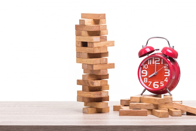 Pile of blocks wood game and red alarm clock on wooden table.
