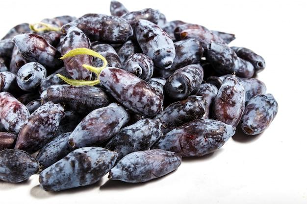 Pile of  blue honeysuckle (lonicera caerulea) or haskap berry isolated