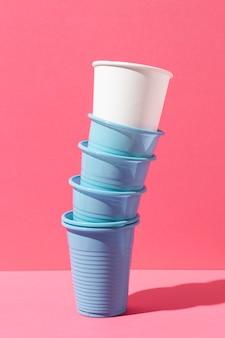 Pila di bicchieri di plastica blu e bicchiere di carta bianca