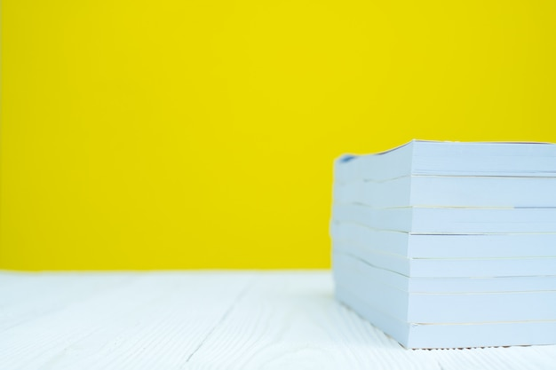 Pile of book on white table with yellow background.