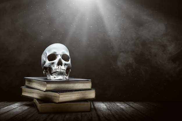 Pile of the book with a human skull on a wooden table
